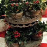 A chic floral centerpiece for any time of the year! Miniature holly plants adorn this vintage cookie stand. Photo credit: Jeffrey A. Tauscher, December 2019